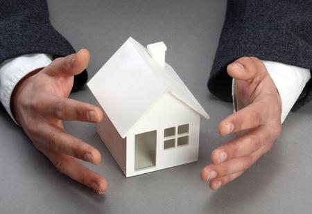 Mani e modello di casa. Beni immobili o il concetto di assicurazione  Archivio Fotografico