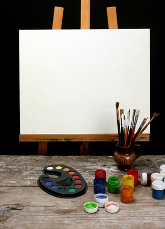 canvas,brushes and easel over black background