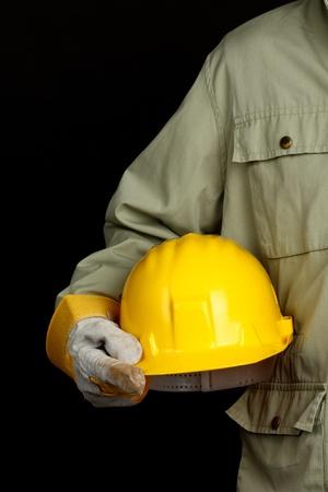 man holding yellow helmet over black background Imagens - 9167086