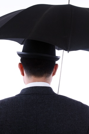 man with bowler hat and an umbrella in the back