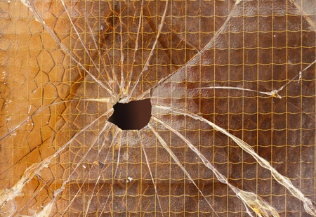 Close up of a broken reinforced glass  cracked with hole  photo