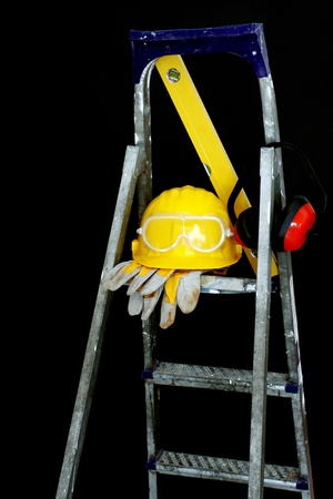 Safety gear kit on step ladder over black photo