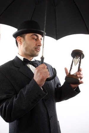 man with bowler hat ,  umbrella  and hour- glass photo