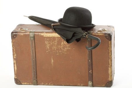 Old suitcase, bowler hat and umbrella over white photo