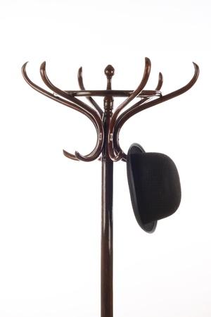 Bowler hat hangs on vintage wooden coat rack over white