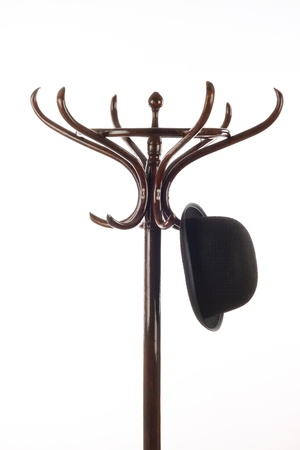 Bowler hat hangs on vintage wooden coat rack over white