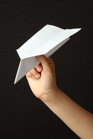 Child hand with paper plane over black background