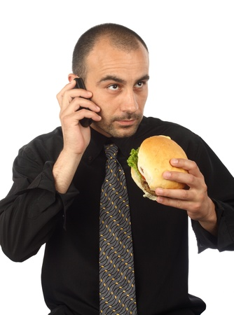 Young businessman eating hamburger, talking by cellphone