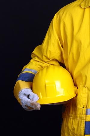 health safety: hombre con casco amarillo sobre fondo negro  Foto de archivo