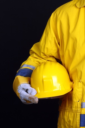 head wear: Man holding casco giallo su sfondo nero