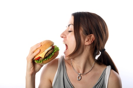 over eating: Young woman eating hamburger over white background Stock Photo