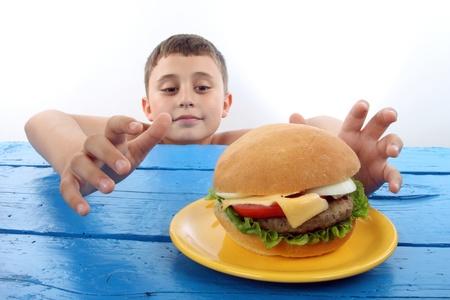 boy grabs a big hamburger close up