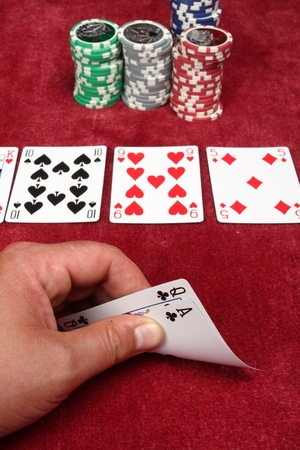 A hand holding two cards in a game of poker photo