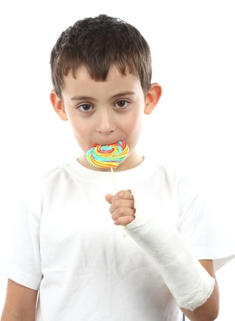 Boy with broken hand in cast, holding a lollipop over white photo