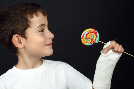 Boy with broken hand in cast, holding a lollipop photo