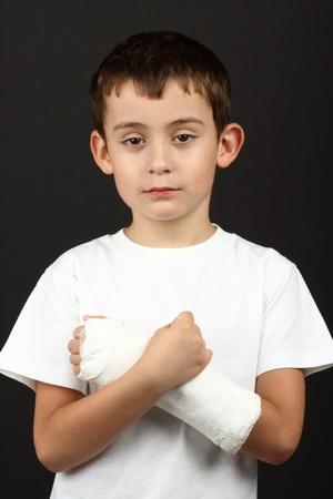 Boy with broken hand in cast, over black Imagens