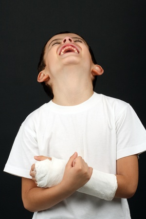 Boy with broken hand in cast, over black photo