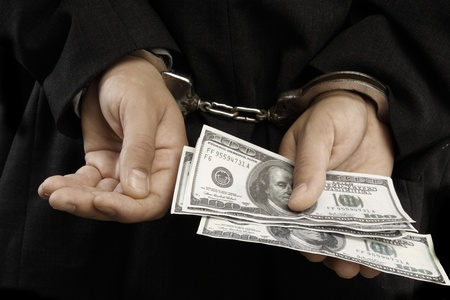 venality: hands in chains giving money Stock Photo