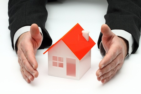 Hands and house model. Real property or insurance concept
