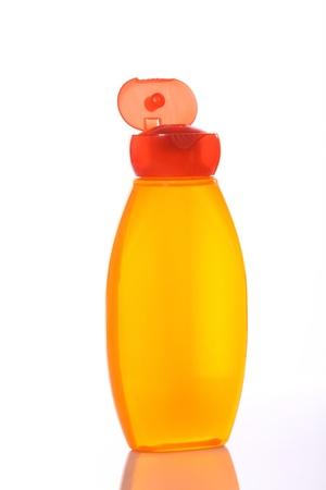 Transparent orange shampoo bottle over white background  Stock Photo - 12916847
