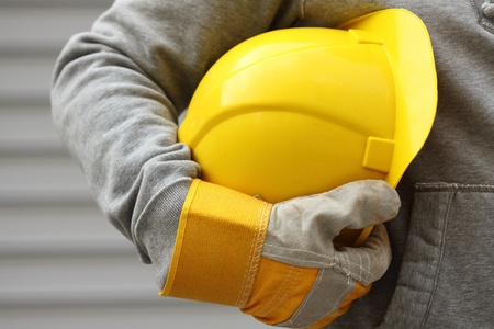 protective wear: Man holding yellow helmet close up Stock Photo