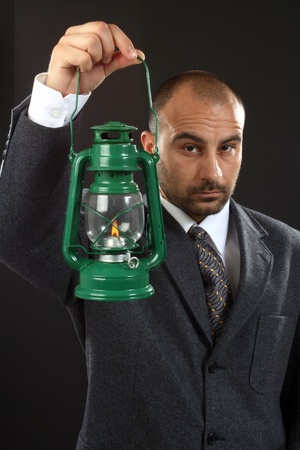Businessman searching for new opportunities with old fashion oil lamp photo