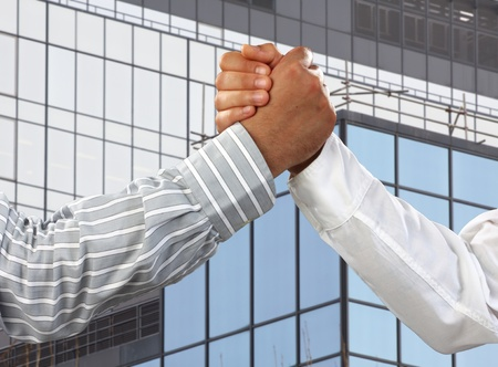 Arm wrestling in the office  over business corporate building photo