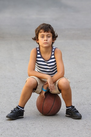Young cute boy with basketball ball photo
