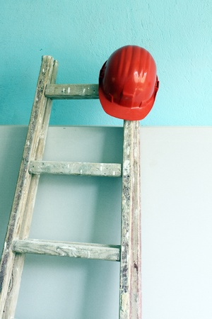 Red helmet and wooden step ladder on work place photo