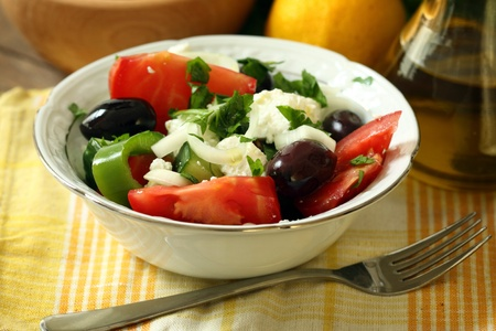 Greek salad with feta cheese, tomatoes, olives and onion photo