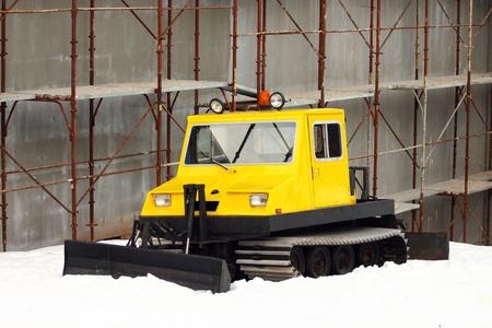 snowcat: small yellow parked snowcat close up