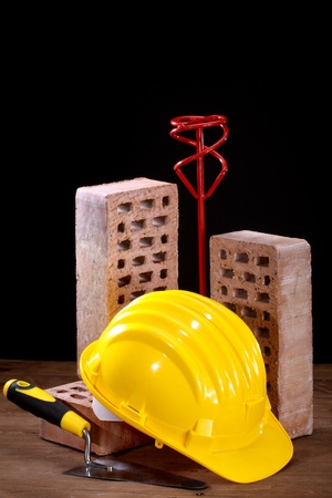 Bricks, trowel and helmet on work place  Stock Photo - 17338776