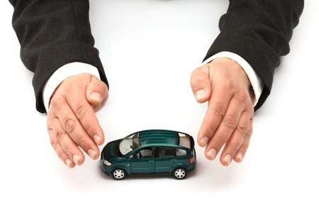 Hands and car model.  Insurance concept
