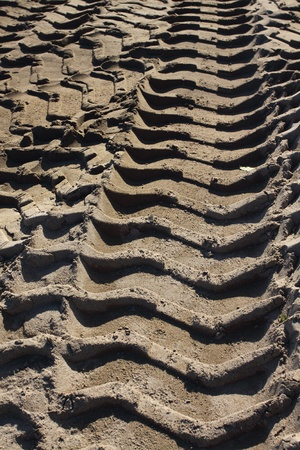 Big heavy tractor wheel tracks in the sand photo
