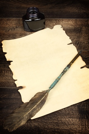 A blank sheet of paper and quill. The desk of an alchemist photo