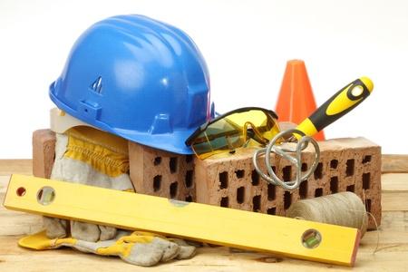 materiales de construccion: Ladrillos, paleta y un casco en el lugar de trabajo Foto de archivo