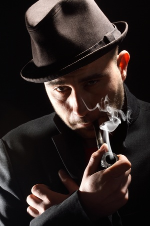 close portrait of a pipe smoker on a black background photo