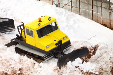 snow grooming machine: small yellow parked snowcat close up