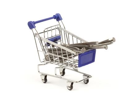 ferreteria: cesta de la compra lleno de grandes clavos. concepto de clavos comerciales Foto de archivo