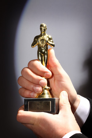 The winner holds in his hand the award. Fake Oscar prize