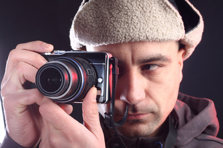 Portrait of young photographer with hat on black photo