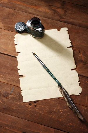 A blank sheet of paper and quill. photo