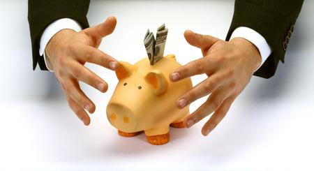 protecting your business: Las manos del hombre de negocios que cubren la hucha