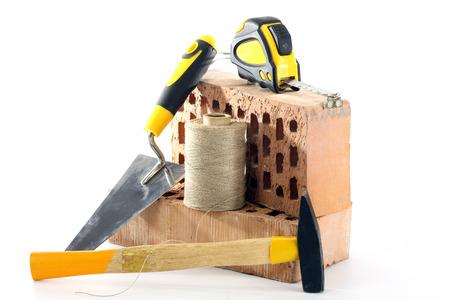 Bricks, trowel and hammer on white