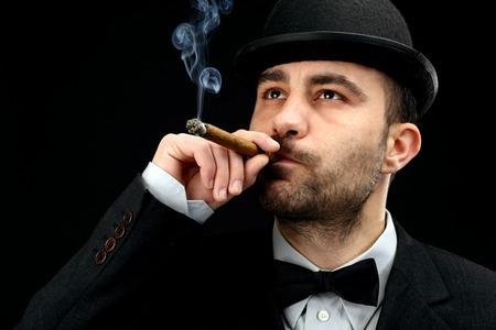 man with bowler hat smoking a  cigar  photo