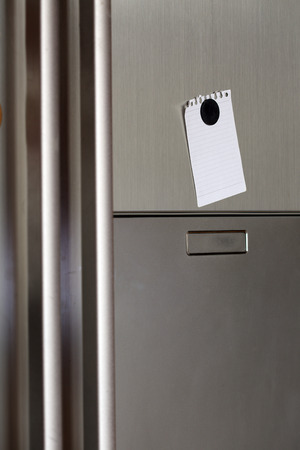 Blank paper and magnet on refrigerator door.  photo