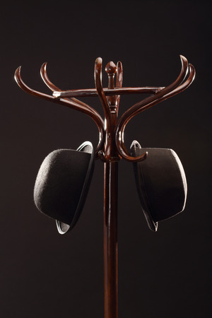 Bowler hats hangs on vintage wooden coat rack over black