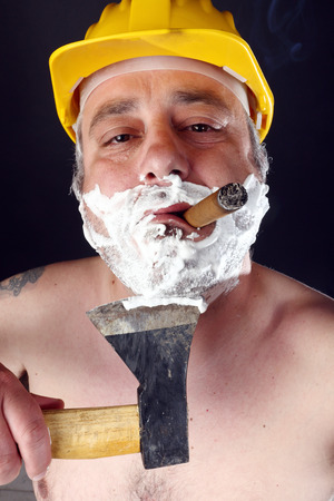 ax man: man with helmet and cigar shave himself with an ax Stock Photo