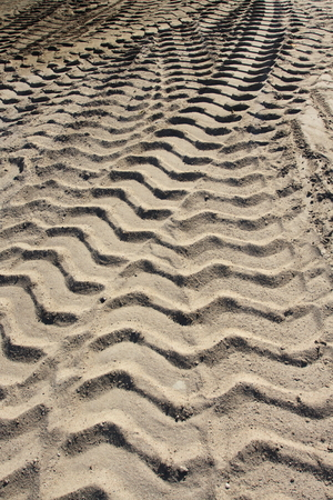 Big heavy tractor wheel tracks in the sand. photo