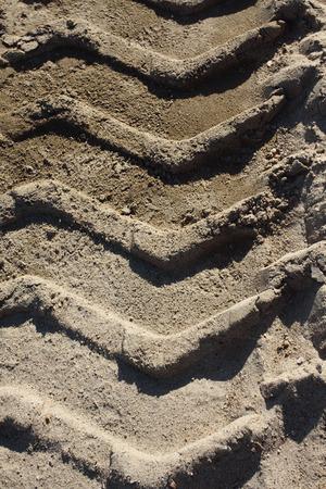 Big heavy tractor wheel tracks in the sand. photo
